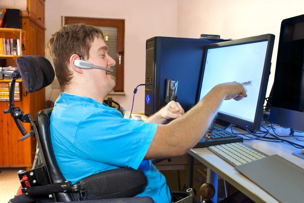 man with cerebral palsy sitiing in front of computer