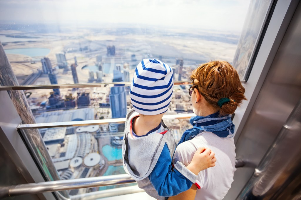 woman and child in an elevator overlooking dubai