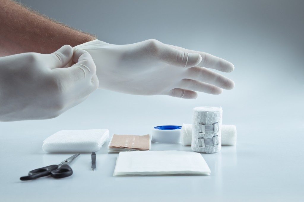 Medical first aid kit and hands with protective gloves