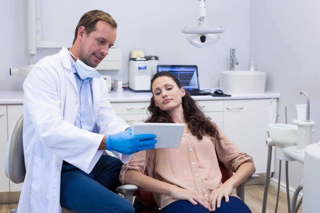 Dentist and patient looking at a tablet