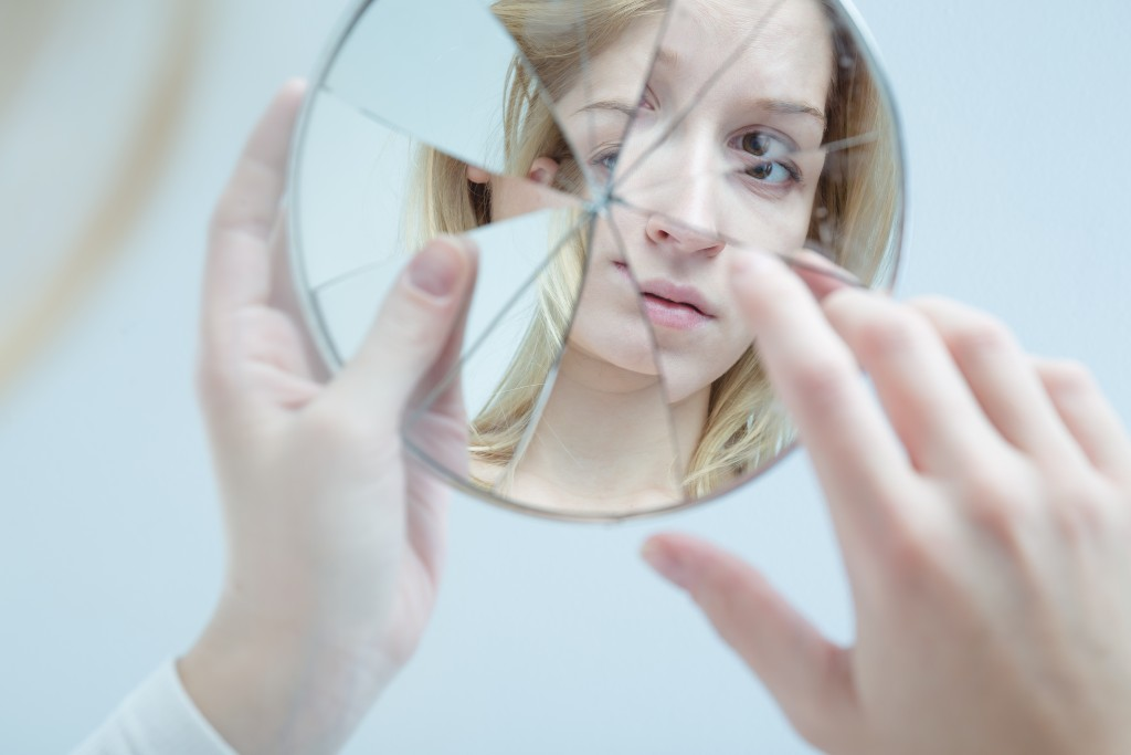 woman holding broken mirror