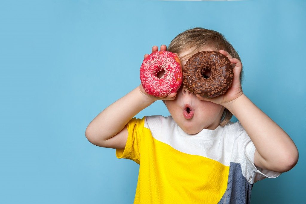 small kid holding doughnuts