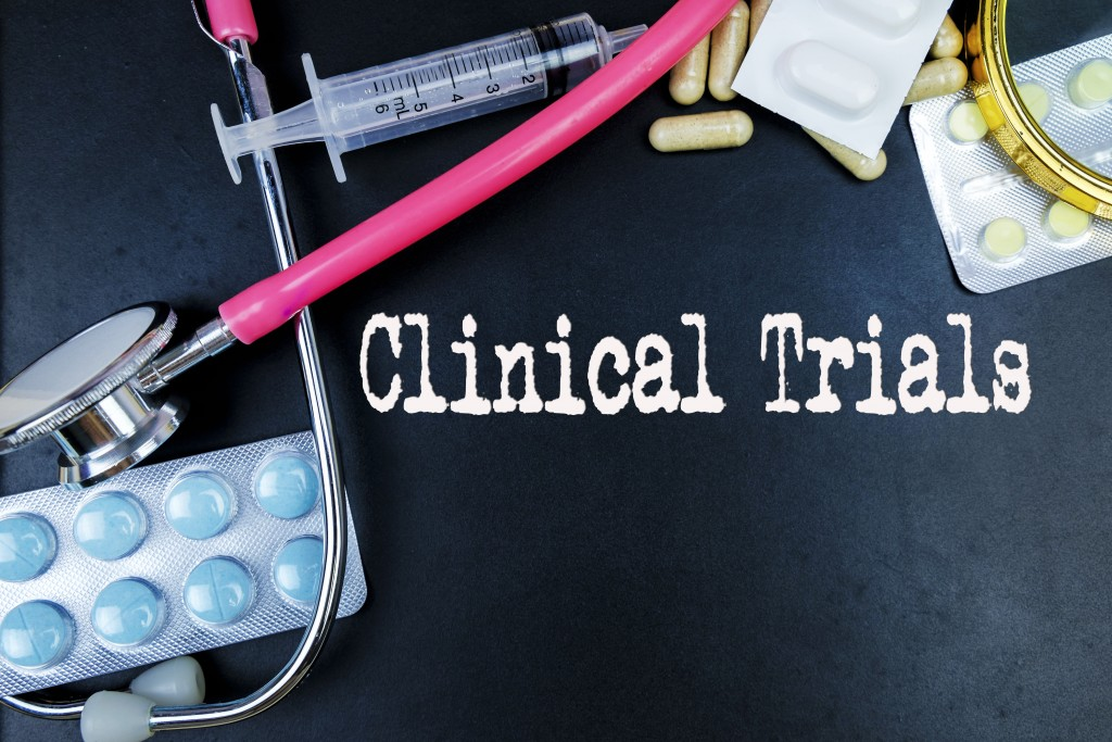 clinical trials word with medicine and medical tools