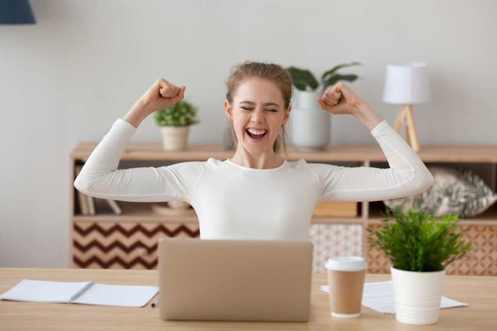 Excited woman looking at her laptop