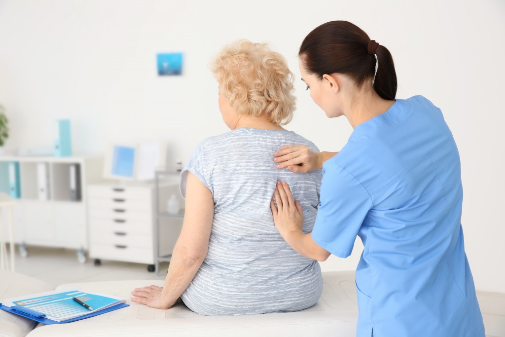 physiotherapist checking on elderly woman's spine