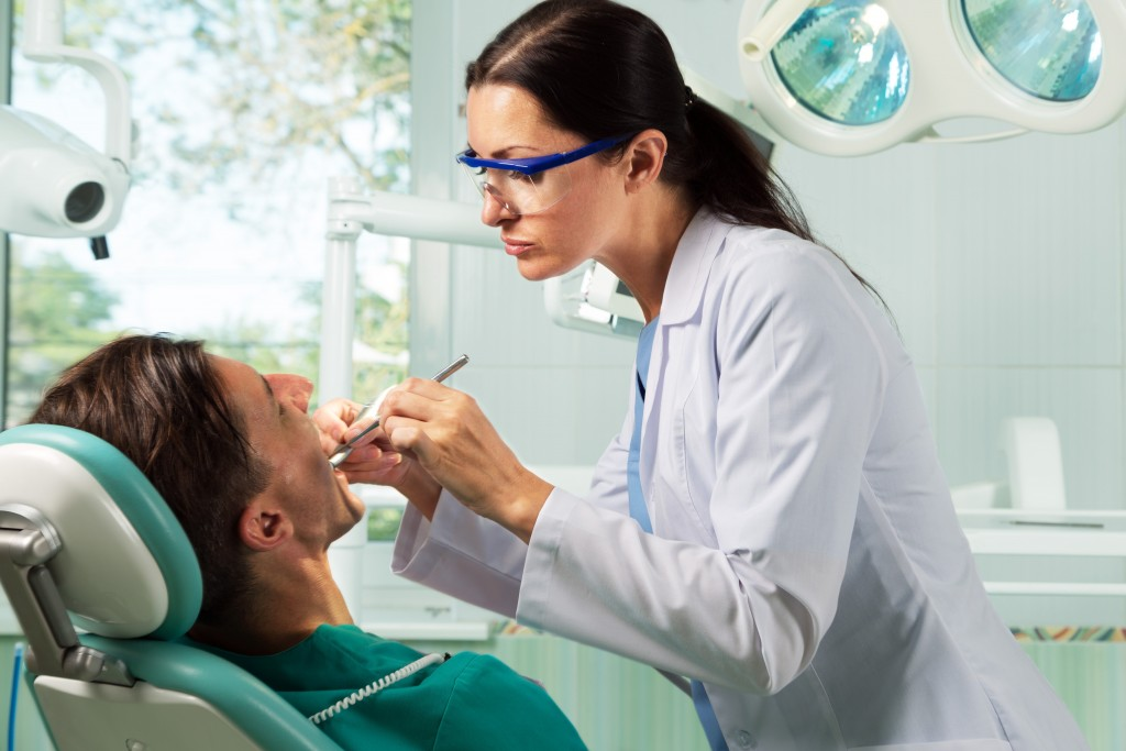 Dentist checking giving her patient a check up