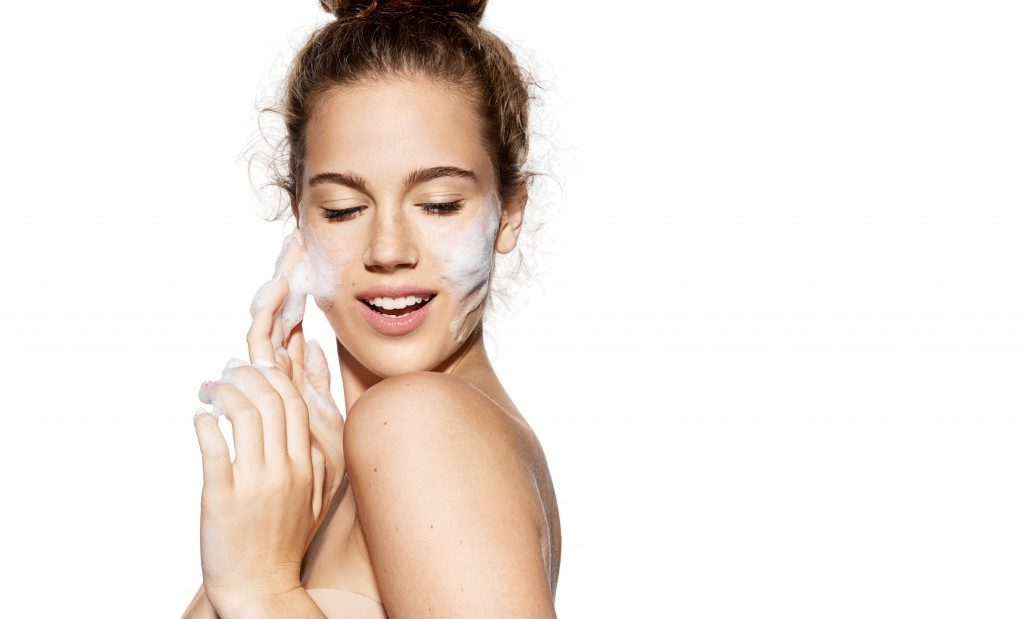 woman applying skincare soap on face