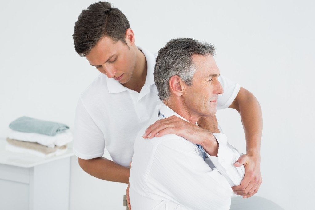 physiotherapist doing adjustments to aged man