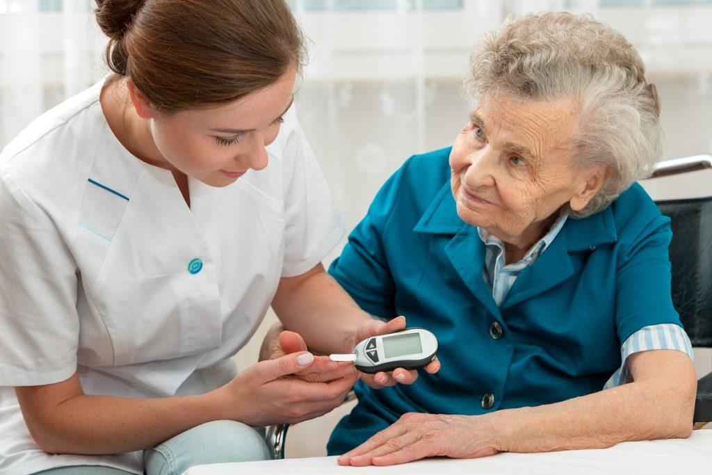 nurse checking blood sugar level of old woman