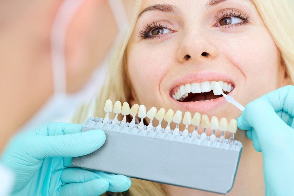 a patient having her teeth check by a dentist for dental implant