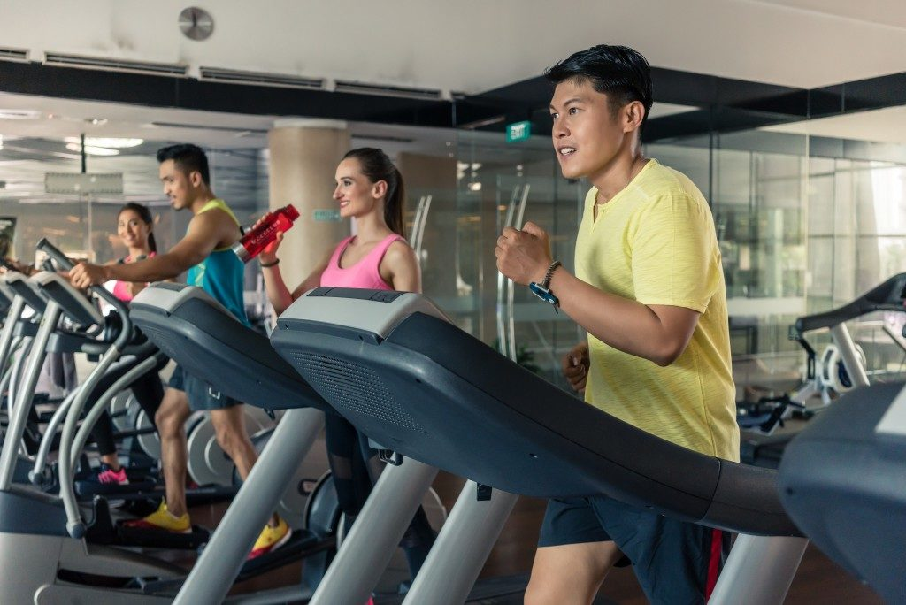 group of people using the treadmill in the gym