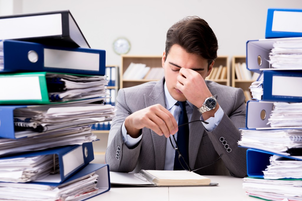 Man with piles of paperwork on his office desk
