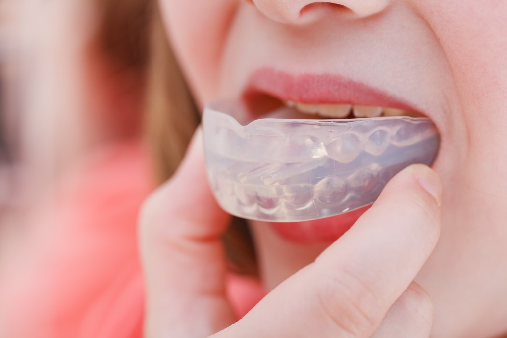 woman putting mouth guard