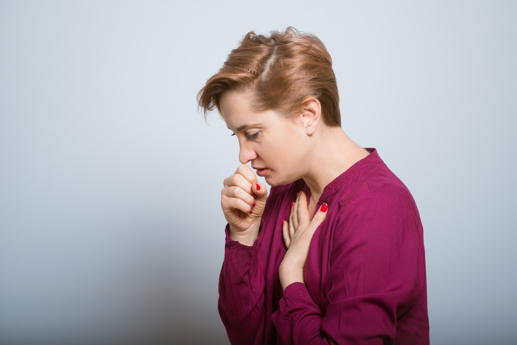 Woman coughing, feeling unwell