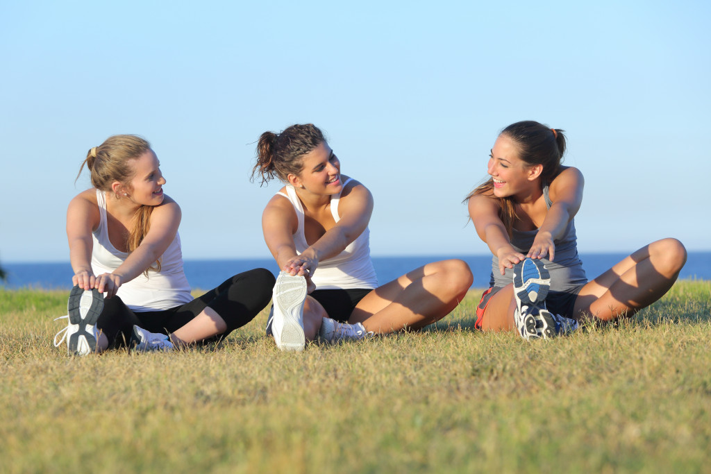 Group of three women stretching after sport on the grass with the sea in the background