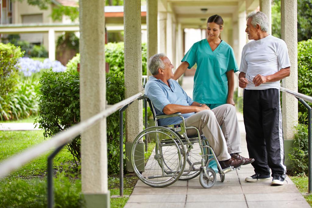 Two senior citizens talking to a nurse in a garden