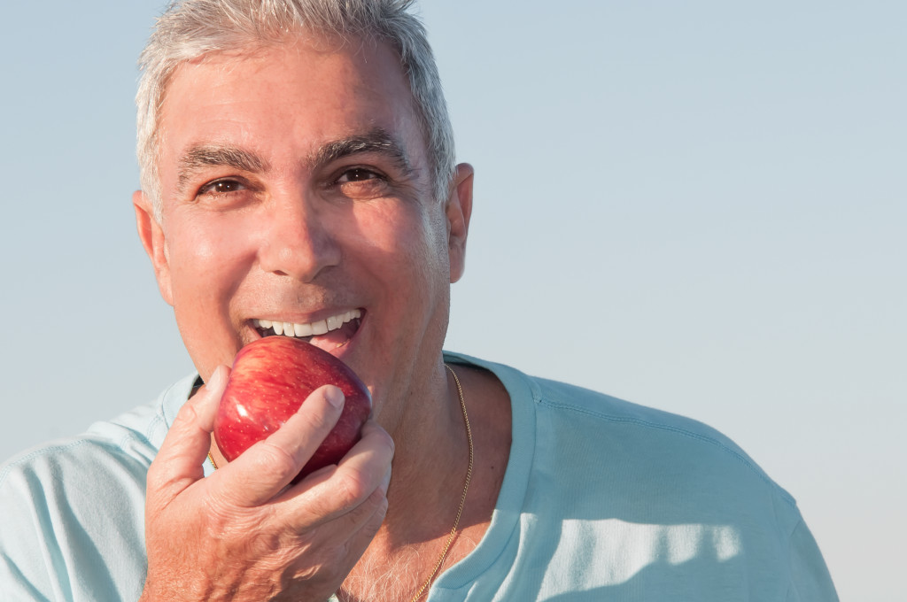 middle aged man eating an apple